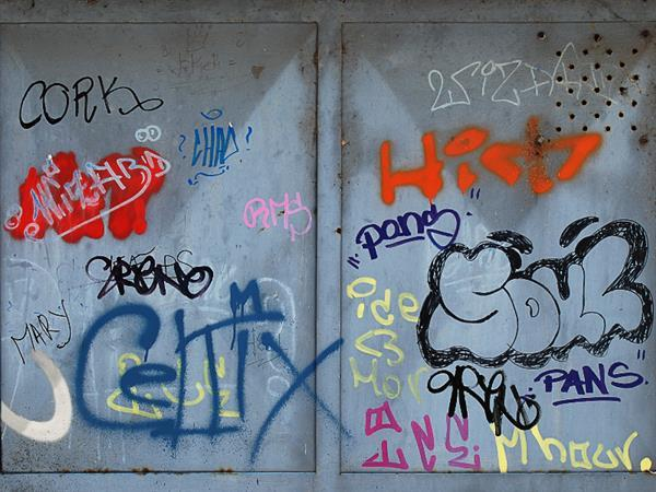 Graffiti spray text on metal warehouse door